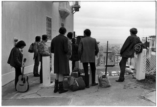 Group of hippies with bags, sleeping bags, and guitar waiting for a ride in San Francisco