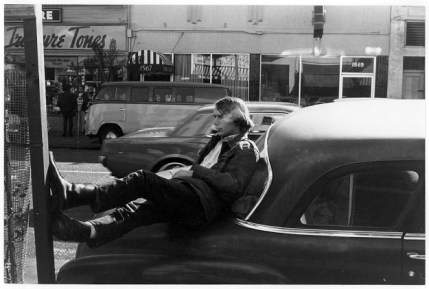 Street scene with man lounging on car
