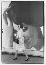 Woman in high heels walking by a large billboard of a woman smoking Tareytons