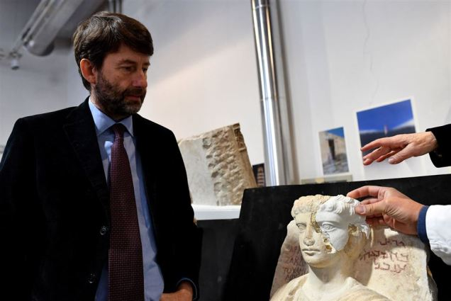 Italian Minister for Cultural Heritage, Activities and Tourism Dario Franceschini (L) looks at a restorer fixing a restored piece of the face of a man bust, which is one of the two funeral reliefs from Palmyra archeological site that will be restored at the Higher Institute of Conservation and Restoration (ISCR - Istituto Superiore per la Conservazione ed il Restauro) in Rome, on February 16, 2017. The busts of a man and a woman, dated from the 2nd and 3rd century AD and destroyed by the Islamic State group (IS), have been entrusted to the care of the technical and restorers of the ISCR in Rome. By the end of this month, they will be returned to their place of origin. Alberto PIZZOLI / AFP