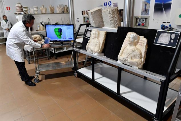 Italian restorer Antonio Iaccarino (L) shows on a computer a 3D model of the two funeral reliefs from Palmyra archeological site that are displayed next to him and that will be restored at the Higher Institute of Conservation and Restoration (ISCR - Istituto Superiore per la Conservazione ed il Restauro) in Rome, on February 16, 2017. The busts of a man and a woman, dated from the 2nd and 3rd century AD and destroyed by the Islamic State group (IS), have been entrusted to the care of the technical and restorers of the ISCR in Rome. By the end of this month, they will be returned to their place of origin. Alberto PIZZOLI / AFP