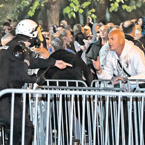 Полицајац настоји да умири демонстранта на недељним протестима у Подгорици (Фото: Ројтерс/Стево Васиљевић)