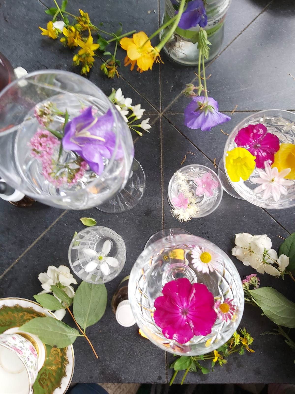 Many glasses of liquid hold vibrant flowers of many colors