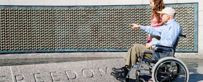 older man in a wheelchair and his grand daughter looking at the stars of the fallen at the world war ii memorial in washington, dc.