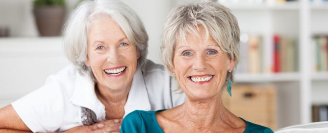 happy vivacious elderly female friends relaxing together in a living room and posing to smile at the camera