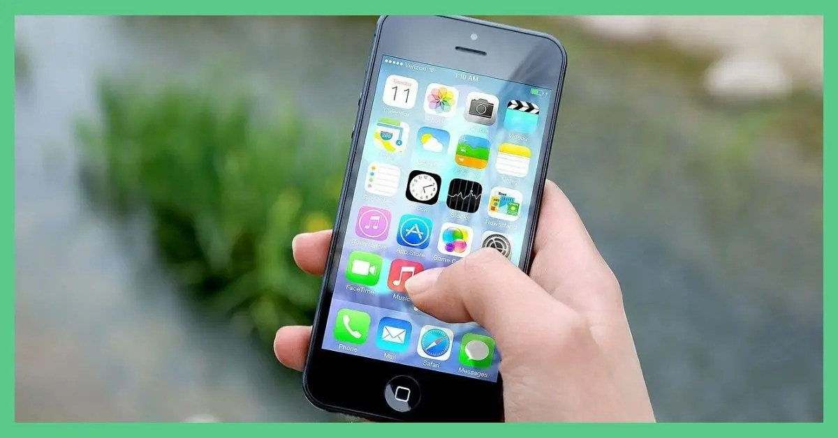Somebody holding an Apple iPhone. The screen is switched on and you can see different apps on the screen. There's some grass and gravel in the background of the image. It's being use as the feature image for 'SIM only vs contract phone: is the saving worth it?'