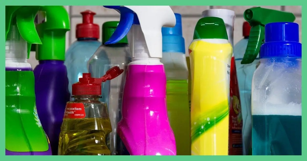 Lots of cleaning bottles lined up next to one another. There is a pink bottle, a yellow bottle, an orange bottle, a green bottle, a purple bottle and a green bottle.