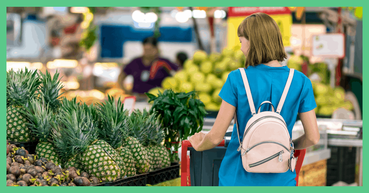 The image shows the back of a woman in a supermarket. She is in the fruit and vegetable aisle. She is wearing a blue t-shire and has a pink backpack on.