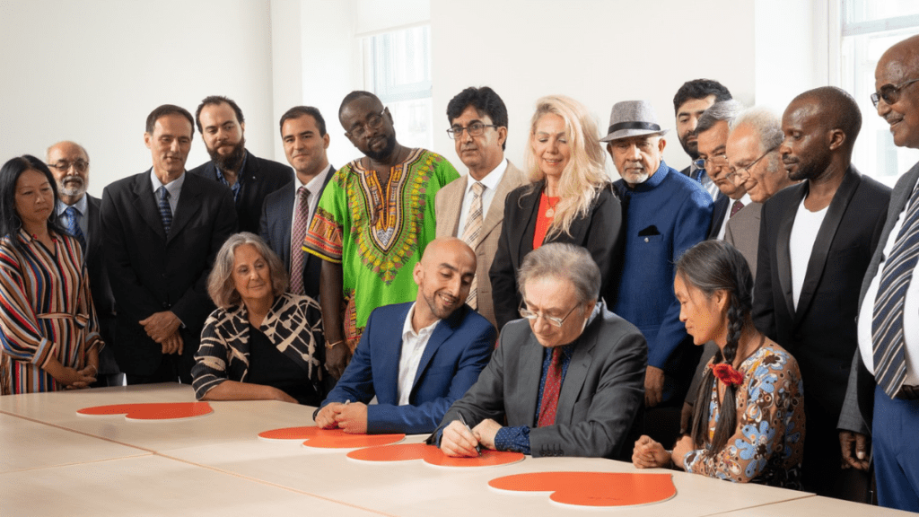 Refugees from 7 decades mark the 70th anniversary of the UN Refugee Convention which took place on 28 July 2021 Left to right standing: Linh Vu (arrived 1979) Bharat Gheewala (arrived 1964) Paul Lorber (arrived 1968) Baraa Halabieh (arrived 2016) Darius Nasimi (arrived 1999) Abu-Zayd Abdulrahman (arrived 2004) Karim Shirin (arrived 1994) Remzije Duli (arrived 1991) Mukund Nathwani (arrived 1972) Ibrahim Dogus (arrived 1991) Dr Nooralhaq Nasimi (arrived 1999) Tom Leimdorfer (arrived 1956) Aloysius Ssali (arrived 2005) Tesfai Berhane Sebhat (arrived 1981) Left to right sitting Gillian Slovo (arrived 1964) Dr Saad Maida (arrived 2010) George Szirtes (arrived 1956) Hong Dam (arrived 1980)