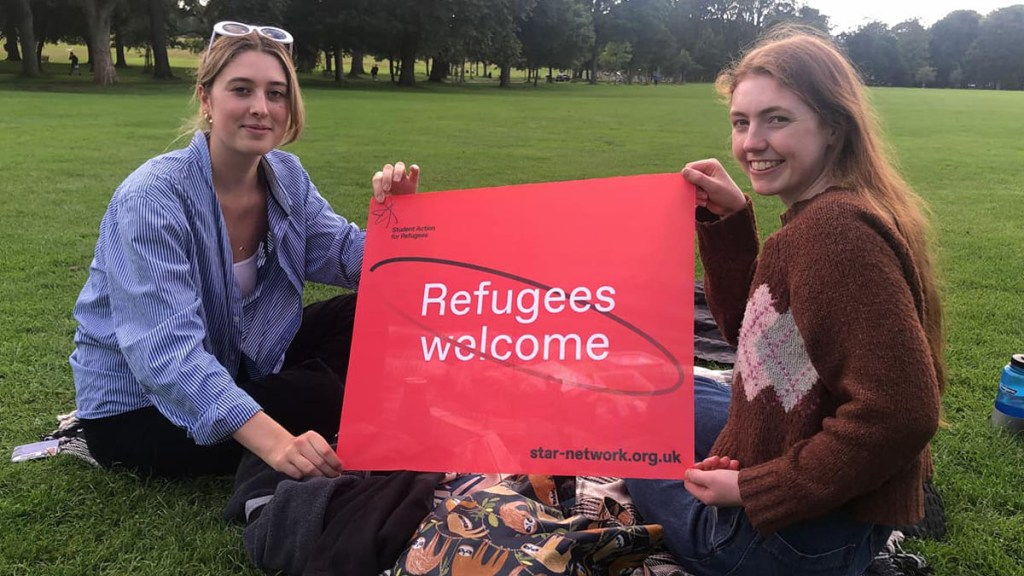 Two students hold a banner that says 'Refugees welcome'