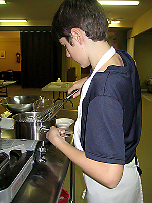 Madison High School freshman Shaun Hannon working on his hollandaise sauce. (Anne Laufe)