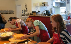 Kaeleigh James and Ellie Asplund slice cakes in half while Claire Asplund patiently waits her turn before slathering butter-cream frosting between cake layers at Portland's Culinary Workshop in Eliot. Kids classes include ages 6-12.