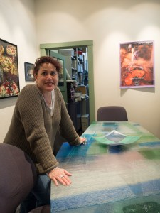 Uroboros systems director Lorna Lovell shows a conference table made from a solid piece of multi-colored glass made at Uroboros.