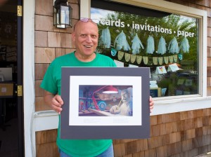 John Field, standing outside Paperjam Press, shows a illustration from his rhyming children's book, Beware. . . Don't Breathe the Air.