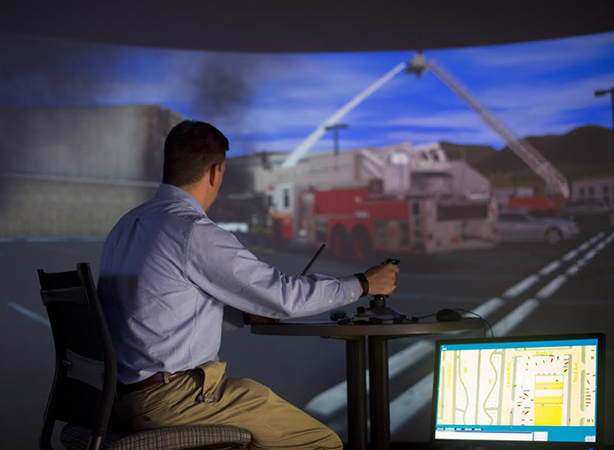 Jason Nairn, director of Concordia University's simulation center, uses a joy stick to 'direct' firefighters in an 'emergency.''  A computerized system projects various scenes on two walls for students to learn disaster management. (Concordia University)