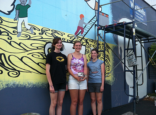 Sophie Tanner, left, Chloe Omelchuck and Meagan Lewis are painting a mural on the Southern wall of Wee Works Preschool in the old Hollywood Library building behind Fleur De Lis bakery. (Ted Perkins)