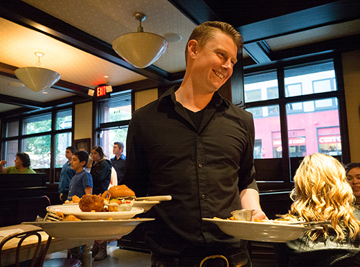 Marcus Chase, general manager at Produce Row Café on Southeast Oak Street, helps clear a table after customers enjoyed burgers and brews at the venerable restaurant located in Buckman.
