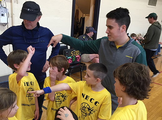 Michael O'Keefe, right, coaches the Killer Bees at Northeast Community Center, on the same gym floor where he learned to play basketball as a first grader – when it was the Northeast Family YMCA and his dad was his coach. (NECC)