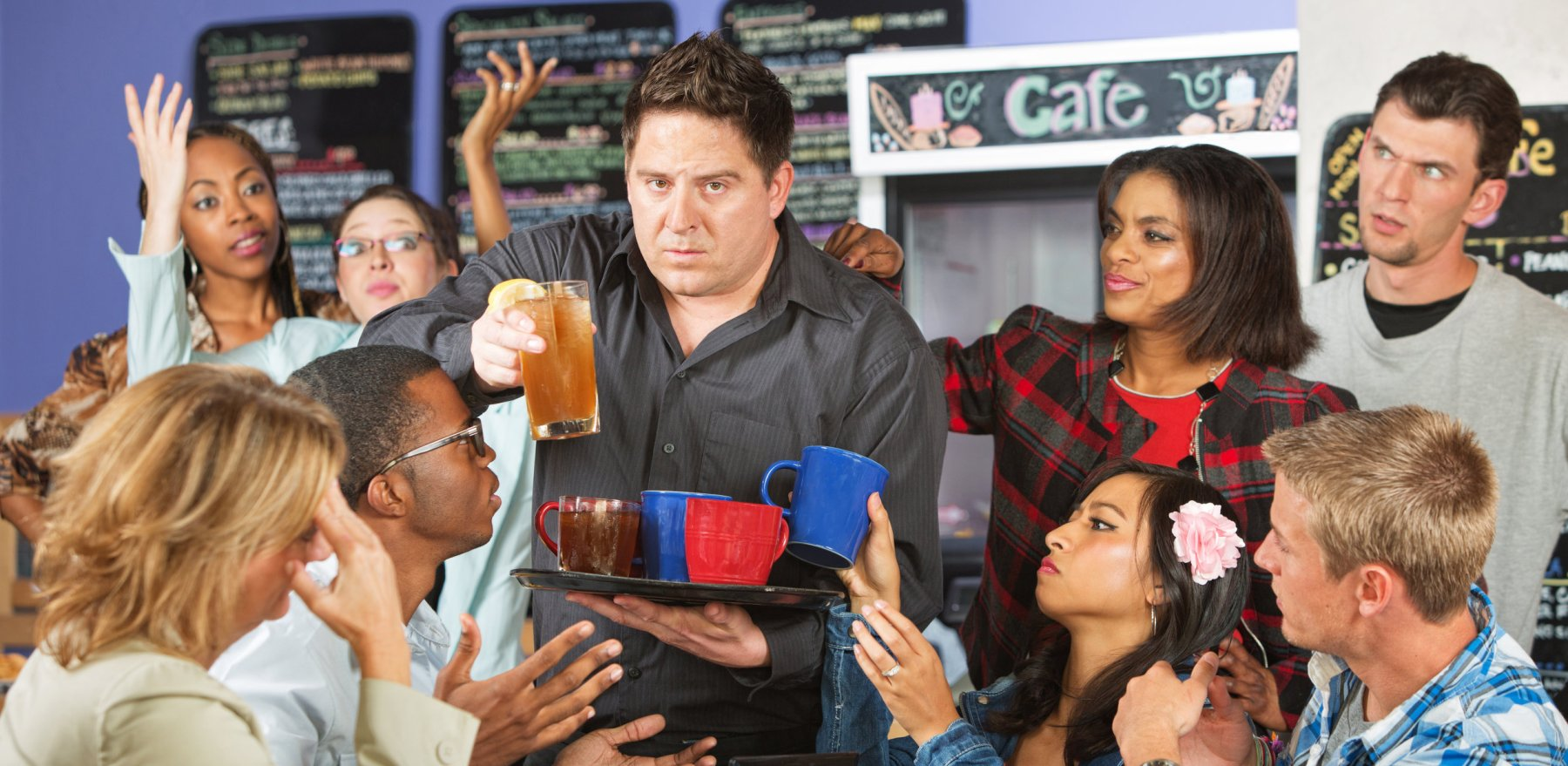 Stressed out restaurant waiter with group of angry customers
