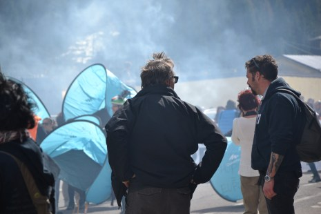 Tents (a symbol for the way refugees live in Idomeni, etc) and blue smoke