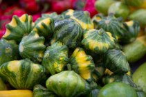 a display of bright green and yellow little pattypan squash at a farmer's market in NYC