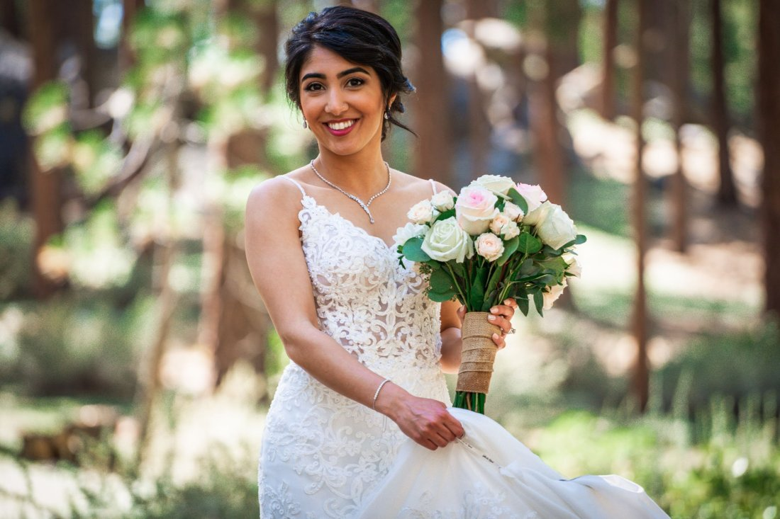 Bride twirling around in her wedding gown, surrounded by pine trees in Lake Tahoe