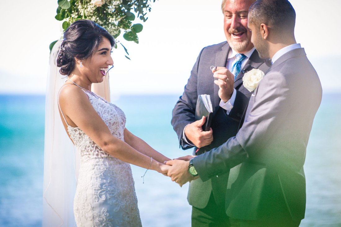 Bride and groom hold hands as the rings are exchanged at their wedding at Regan Beach