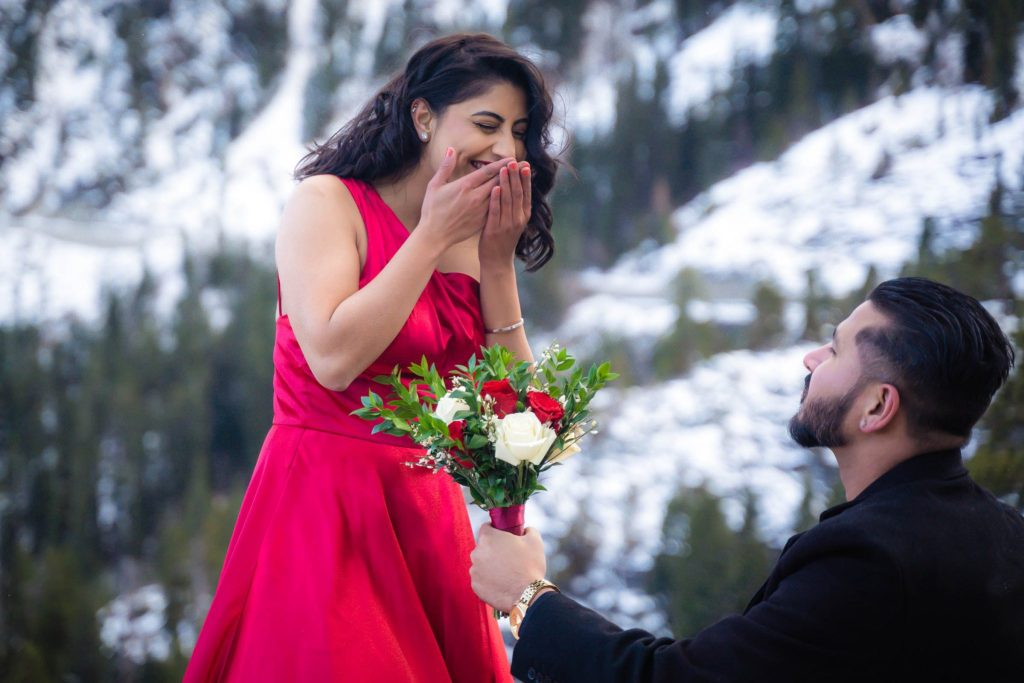 Offering roses to his fiancee during their engagement session at Vikingsholm, Emerald Bay