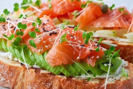 two-open-sandwich-toast-with-salmon-cream-cheese-avocado-cucumber-slices-on-white-concrete-table_t20_E0e10X