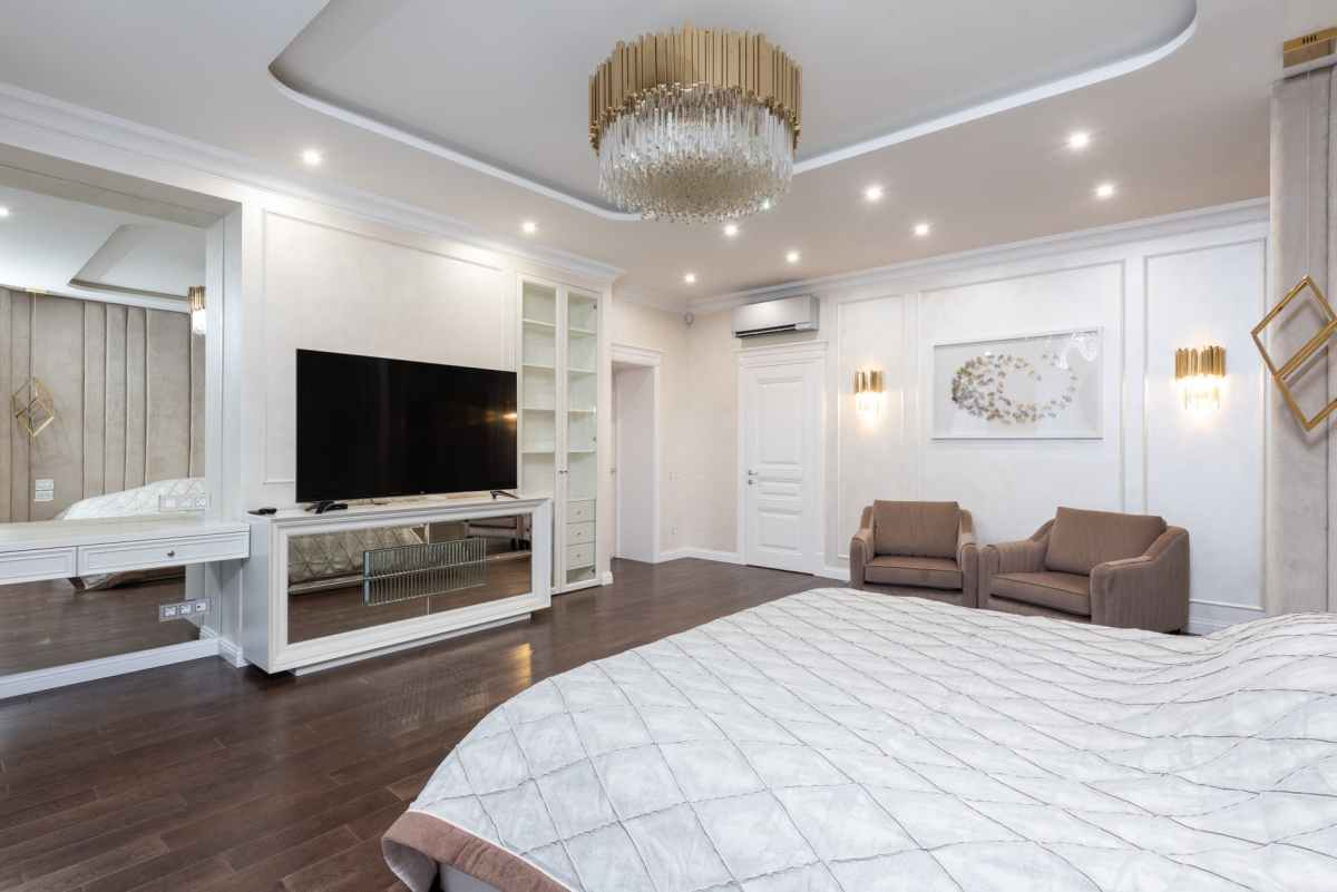 classic bedroom with armchairs and tv next to bed