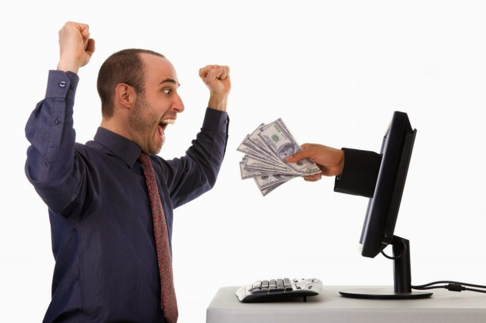 Man winning cash from laptop