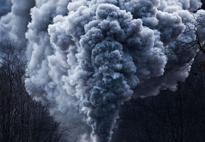 Powerful steel engines blowing huge, undulating clouds of smoke into the air eme…