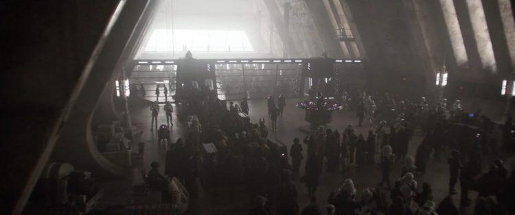 Vervolgens zien we een grote hal waar een hoop wezens in een rij staan te wachten terwijl Stormtroopers een oogje in het zijl houden.