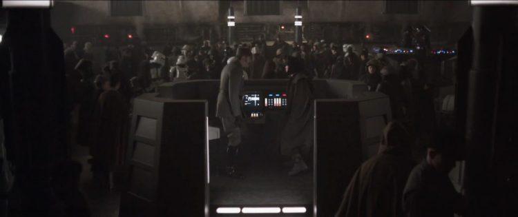 We zien een Imperial officier en een persoon die verhuld is in een lange jas en muts gaan zitten in een afgebakend kantoortje in diezelfde ruimte.