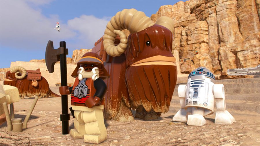 Lando in his Jabba's palace disguise with R2-D2 and a bantha in LEGO Star Wars: The Skywalker Saga.