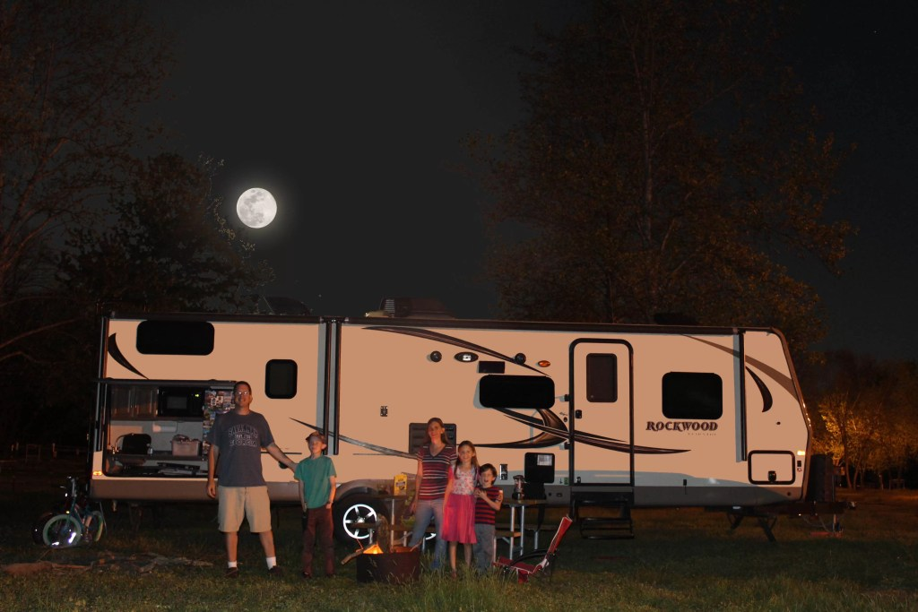 Family in front of Travel Trailer at night
