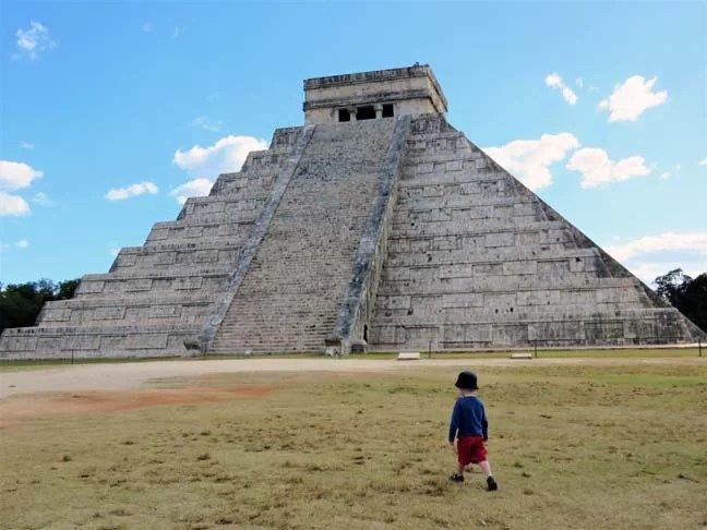 A boy walking in front of a pyramid