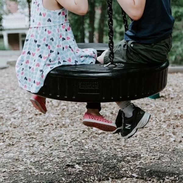 Two kids on a tire swing