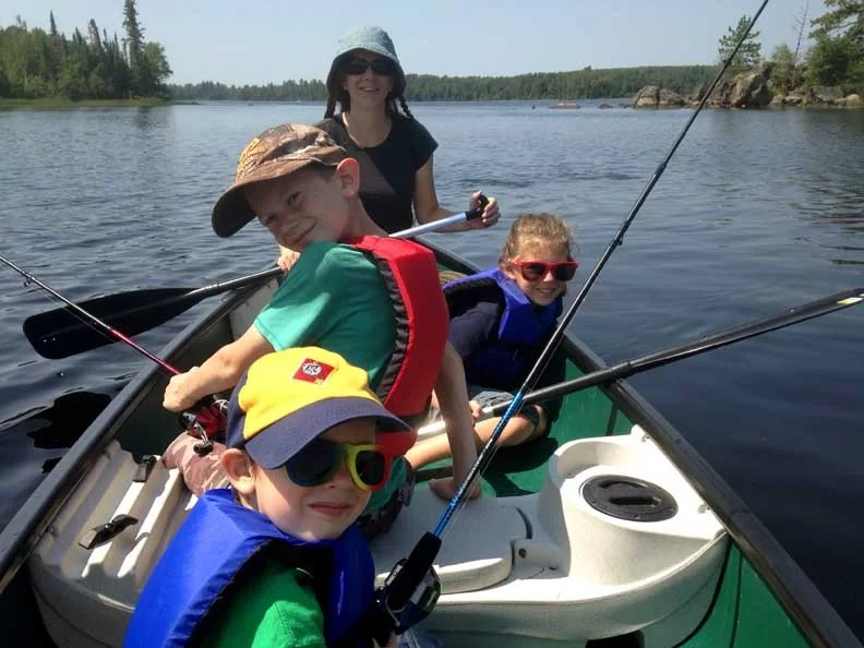 Family fishing from a canoe in Minnesota.