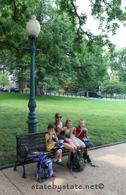 Family eating a picnic on a bench.