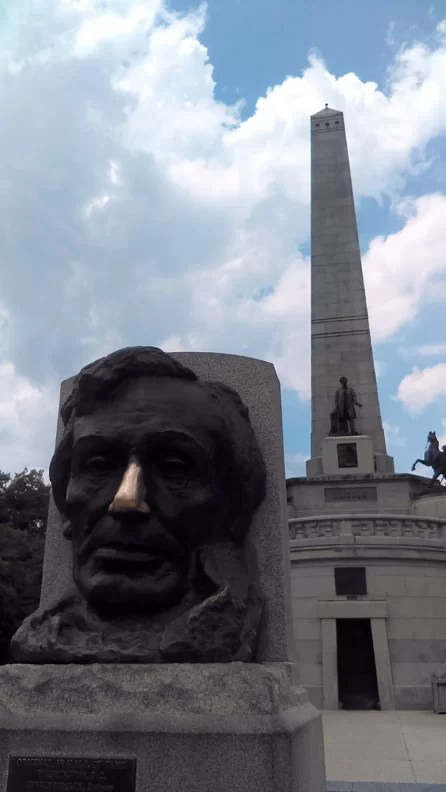 A statue of Lincoln with his tomb monument in the back ground.