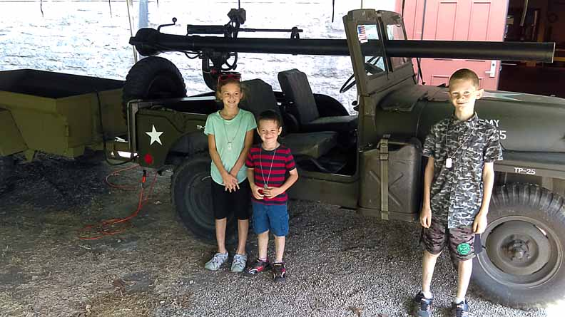 Three kids in front of a jeep with a cannon on top.