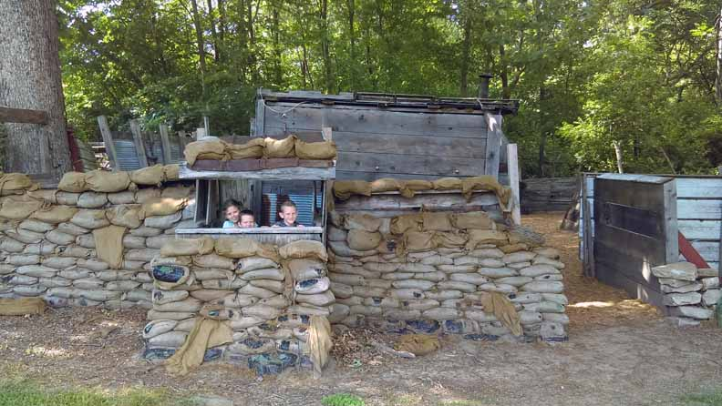 Three kids in a trench bunker.