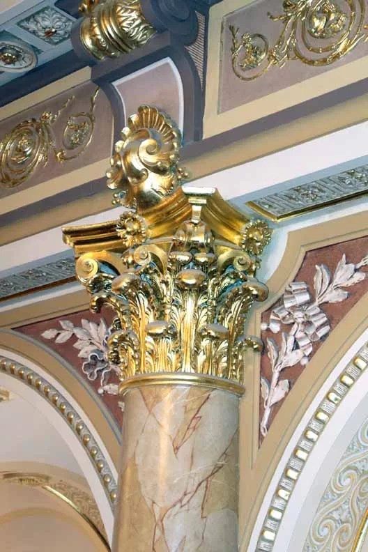 The beautiful gold leafed top of a marble piller.