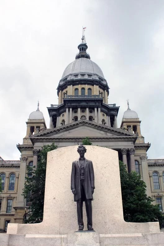 Illinois capitol building with a statue of Lincoln in the foreground.