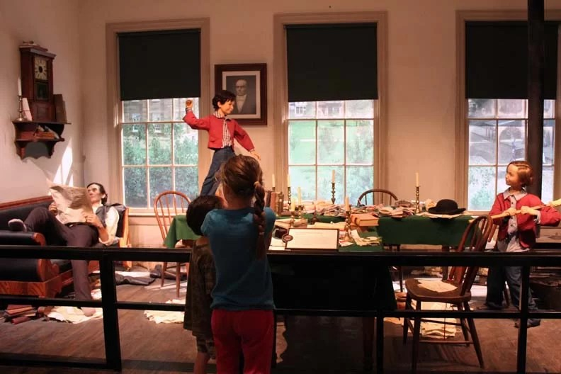 Wax statues of Lincoln reading a paper and his two sons playing ball on the table.