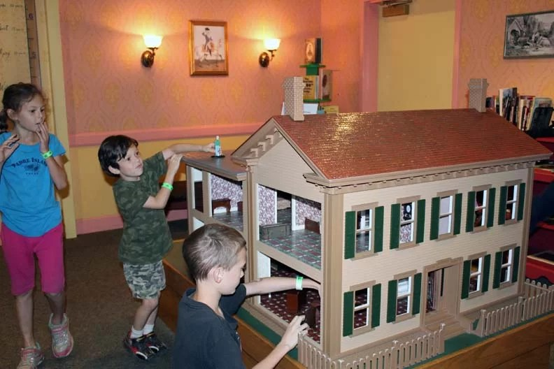 Three kids playing with a doll house.