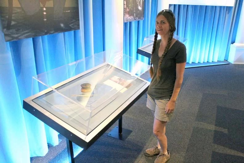 A woman standing next to a display with the pen that signed the Emancipation Proclimation.