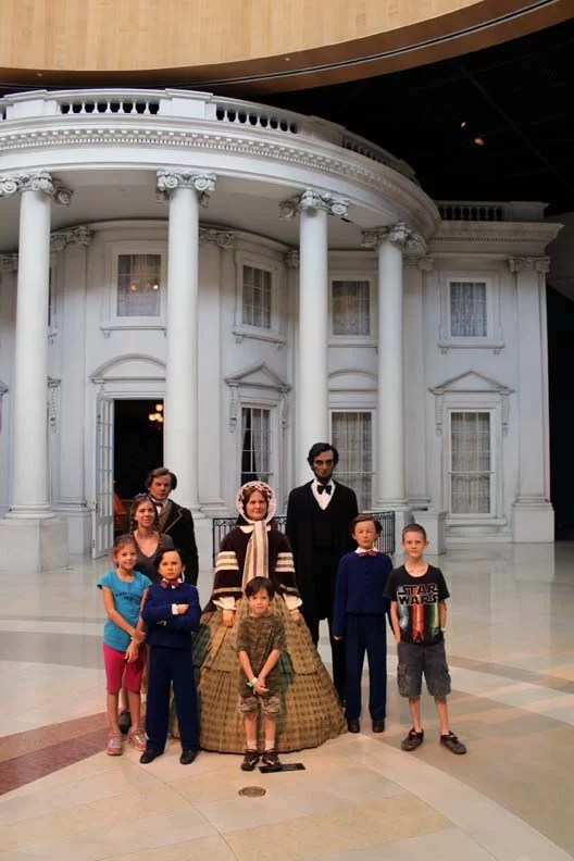 A family posing with Lincoln's family done very realistically in wax.