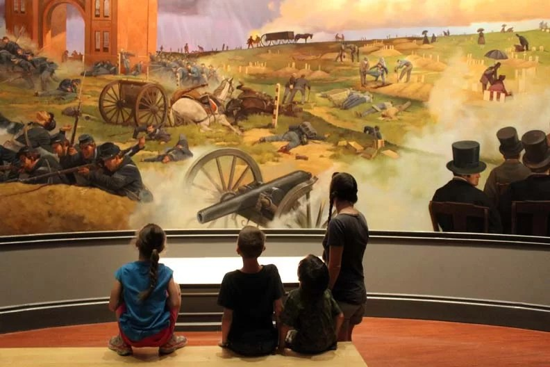 An epic battle scene painting with a family sitting in wonder before it.